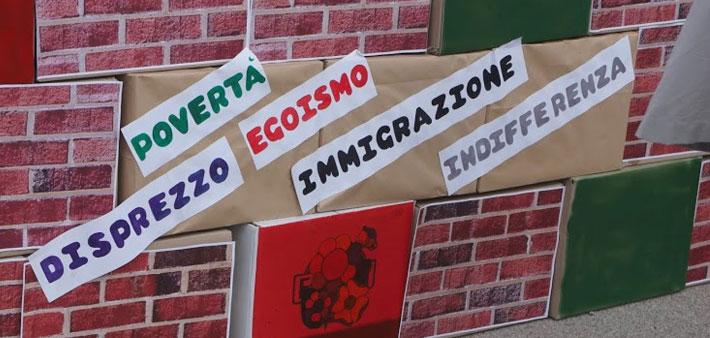Ramazza Arcobaleno, la manifestazione a Roma per spazzare via le disuguaglianze. Il muro costruito da volontari e bambini riporta le scritte: immigrazione, indifferenza, disprezzo, povertà, egoismo