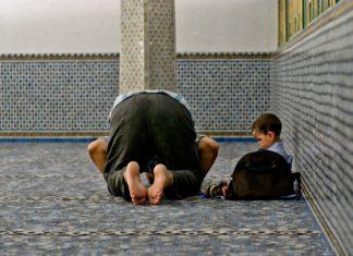 Musulmano che prega alla moschea con bambino