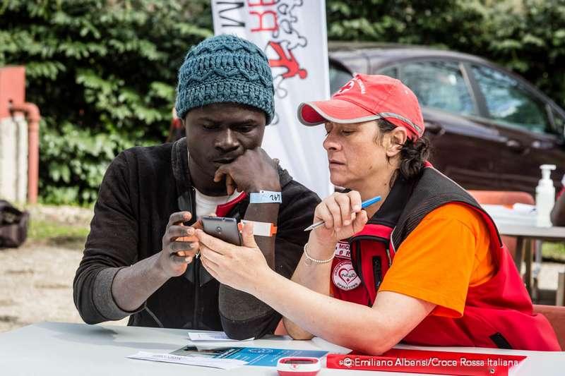 Un'operatrice Croce Rossa aiuta un migrante a comporre il numero di telefono. Migranti telefonano alle famiglie dal camper della Croce Rossa. Foto: Emiliano Albensi