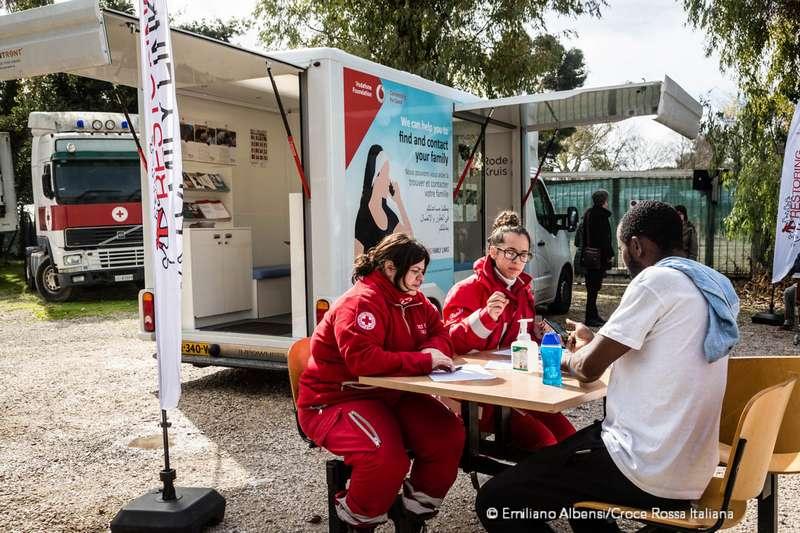 Volontarie Croce Rossa parlano con un ragazo migrante vicino al tracing bus. Migranti telefonano alle famiglie dal camper della Croce Rossa. Foto: Emiliano Albensi