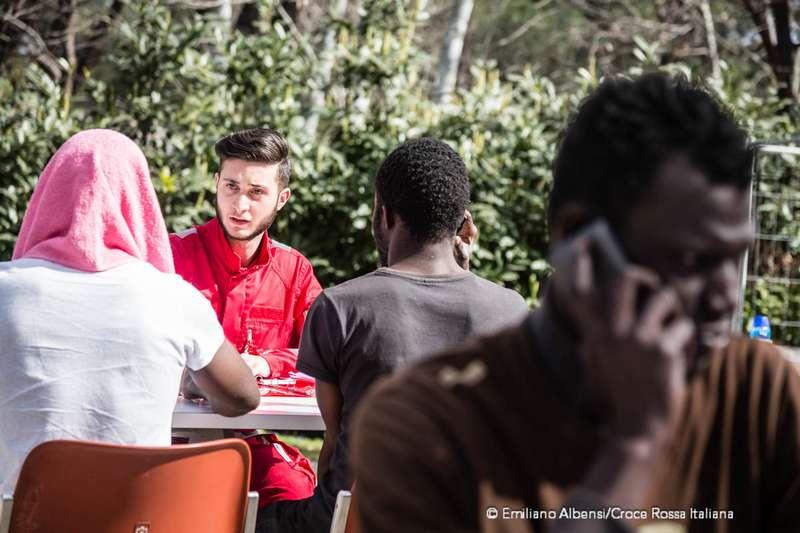 Un volontario croce rossa parla con alcuni ragazzi migranti che vogliono chiamare la famiglia. Migranti telefonano alle famiglie dal camper della Croce Rossa. Foto: Emiliano Albensi