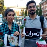 Ragazzi iraniani mostrano cartelli scritti in farsi per esprimere solidarietà alle vittime dell'attentato a Teheran
