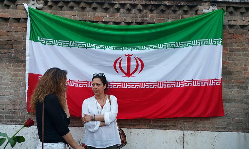 Due ragazze parlano davanti alla bandiera dell'Iran esposta a Roma per commemorare le vittime dell'attentato terroristico del 7 giugno 2017