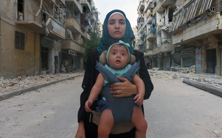 Nel film For Sama la giornalista con in braccio la figlia, Sama, tra le macerie di Aleppo